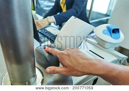 Biometric control in airport. Woman puts her finger on scanner at the control post
