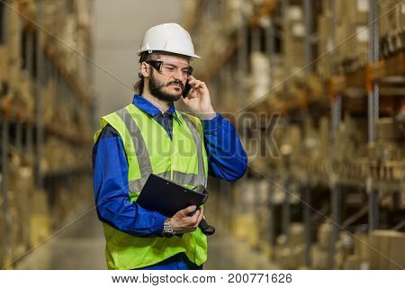 Warehouse worker in hard hat and uniform speaking on mobile phone