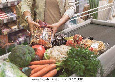 Adult lady is putting pasta pack at cash register tape. Different vegetables and fruits are there. Focus on products. Close up of female hands