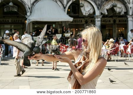 Girl holding pigeons in Piazza San Marco Venice Italy. Pigeons once rivaled cats as the traditional, if unofficial, mascots of Venice. Photo taken 23.06.2010