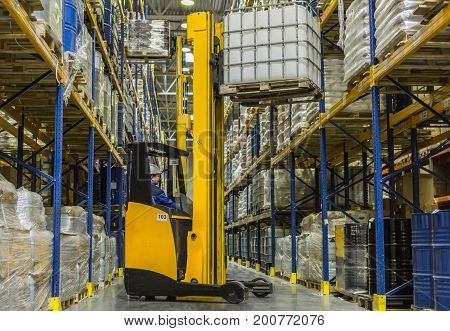 Warehouse worker on stacker loading cargo on rack