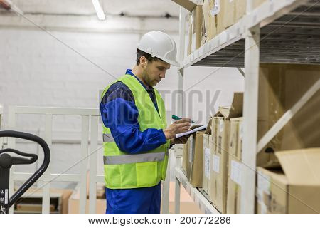 Warehouse worker in hard hat and glasses looking at documents
