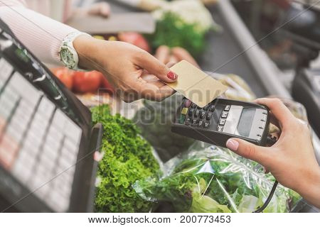 Woman is going to use contactless means of payment in supermarket. Close up of female hands holding necessary cash equipment