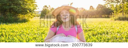 Close up portrait on cute laughing or surprised woman with freckles in hat.
