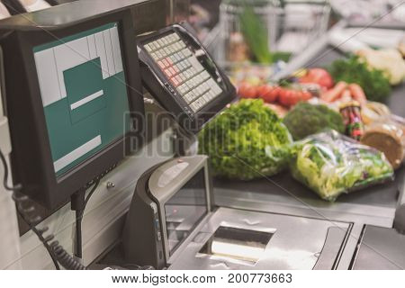 Necessary electronic devices at supermarket. Cash register ready for using. Different goods on tape. Copy space on right side