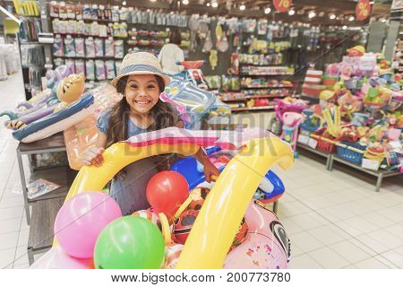 Joyous little girl is standing near different inflatable things for sea vacation and wants to buy them. She looking at camera with smile. Portrait. Copy space on right side