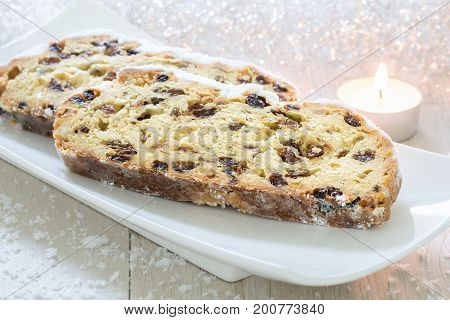 Christmas Stollen on a white plate with candle