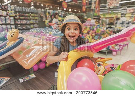 I want this. Crazy little lady is clutching big inflatable toy and looking at camera with great astonishment. Portrait. Copy space on left side