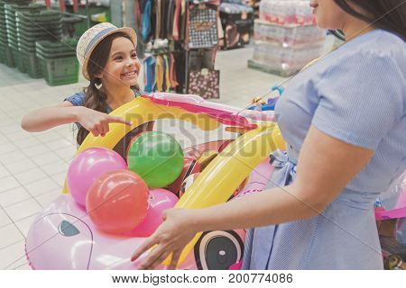 Cheerful little lady is pointing on big toy and looking at mother with bright smile. They standing in supermarket