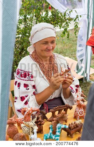 ADYGEA RUSSIA - AUGUST 19 2017: cheerful woman in the shop with clay Souvenirs and toys at the festival of cheese Adyghe in Adygea