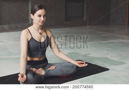 Young woman in yoga class, meditation exercises. Girl does lotus pose for relaxation. Healthy lifestyle in fitness club
