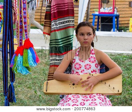ADYGEA RUSSIA - AUGUST 19 2017: sad girl playing music on the harp at the festival of cheese Adyghe in Adygea
