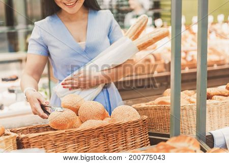 Cheerful female consumer is taking small palatable bun from basket. She holding two baguettes. Copy space on right side