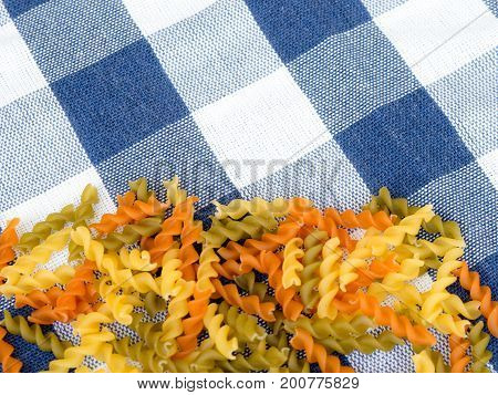 Background of colorful pasta texture close-up. close up of a dried italian pasta onblue plaid tablecloth.Colored natural pasta