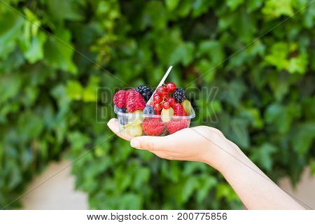 healthy eating, dieting, vegetarian food and people concept - close up of woman hands holding berries outdoor.