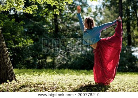 Yoga outdoors. Sporty fit caucasian woman in red skirt doing Ashtanga Vinyasa Yoga asana Virabhadrasana 2 Warrior pose posture in nature. Blurred view.
