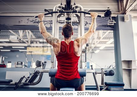 Strong Bearded Bodybuilder Doing Heavy Weight Exercise For Back On Machine.