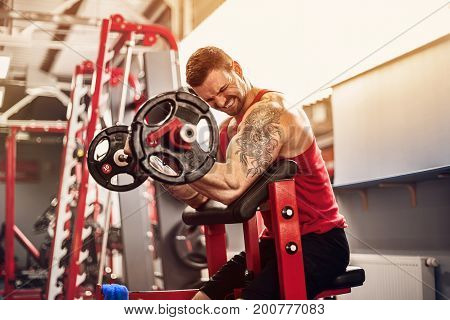 Bearded tattoed Man bodybuilder doing the set of a barbell exercise in a gym. Real time shot