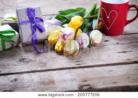 Yellow and white spring tulips wrapped boxes with presents and red cup with heart on vintage wooden background. Selective focus is on presents. Place for text.