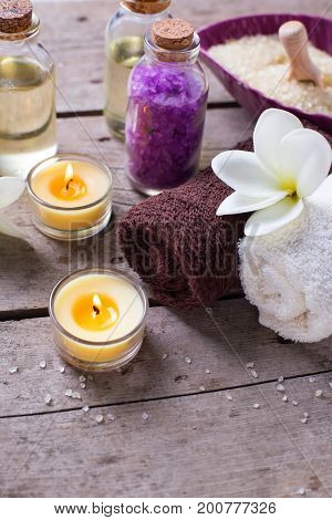 Wellness or spa setting. Bottles with aroma oil sea salt towels and white plumeria flowers on wooden background. Selective focus. Place for text.