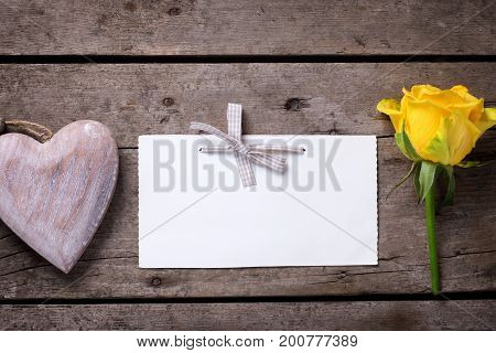 Background with yellow rose decorative heart and empty tag on wooden table. Selective focus is on tag. Place for text.