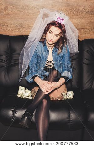 pensive fiance sitting on sofa with dollars and looking away