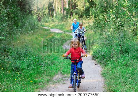 active senior with grandkids riding bikes in summer nature