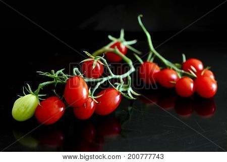 A bunch of oblong cherry tomatoes on the black background