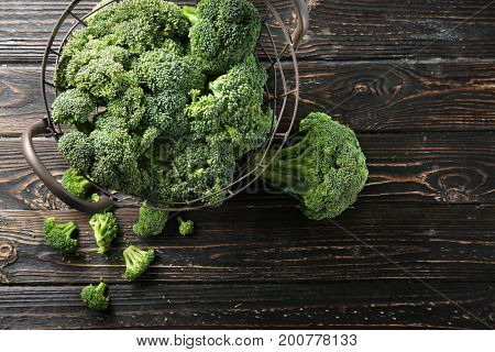 Fresh green broccoli in basket on brown wooden table