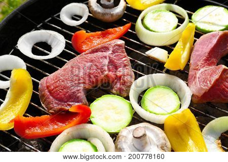 Cooking tasty beefsteaks and vegetables on barbecue grill outdoors, close up