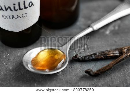 Spoon with aromatic extract and dry vanilla beans on table