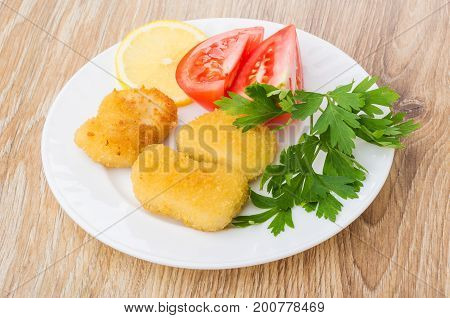 Chicken Nuggets With Tomatoes, Lemon And Parsley In Plate