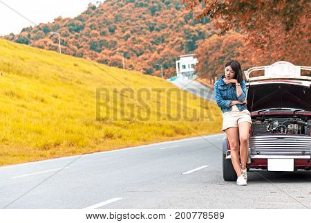Young woman waiting help at broken down car on street. Vintage tone.