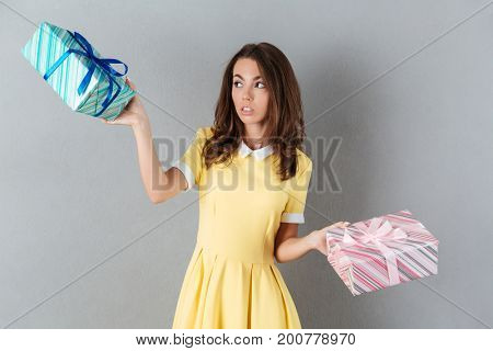 Indecisive young girl choosing a present box while standing isolated over gray background