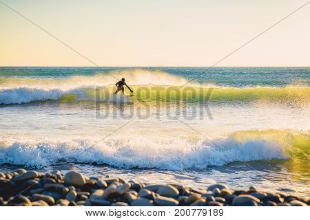 Surfer in wet suit on wave at sunset or sunrise. Surfer in ocean and waves