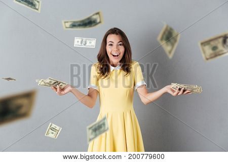 Picture of happy young caucasian lady standing over levitate money over grey background. Looking camera.