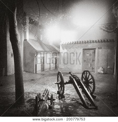 Prague Czech Republic: paved lighted streets houses lantern cannon. Night. low-rise building with a door the writing on the wall sloping roofs. BW photo