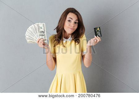 Picture of thinking young caucasian lady holding money and debit card in hands. Looking aside.