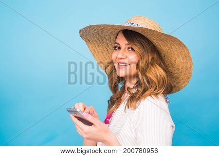 Technology, people and modern devices concept - Smiling Woman writing in phone, texting message side view on blue background with copy space