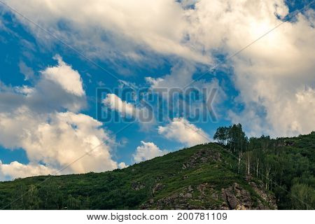 A woody and rocky hill lit by bright sun rays in the summer morning Altai Mountains Kazakhstan