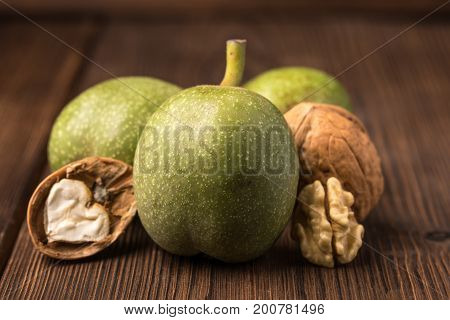 Fresh Harvest Of Walnuts On A Wooden Background. Green And Brown Nuts. Shell And Peel Of Walnuts.