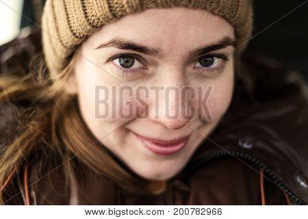 Selfie of happy beautiful Caucasian woman in a woolen hat in a car in winter.