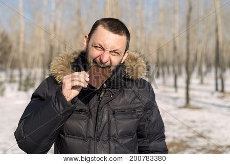 Young man eating chocolate outdoors in a winter forest.