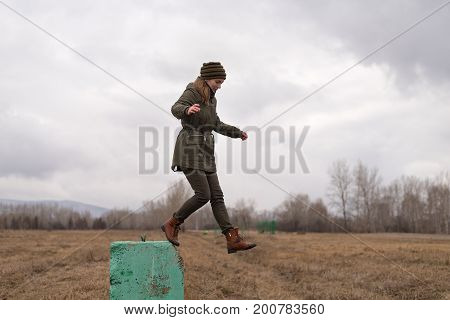 Young hipster woman jumping from a concrete block in the park on a spring cloudy day.