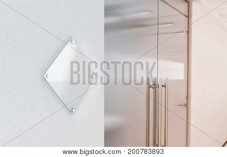 Blank rhombus transparent glass sign plate mockup 3d rendering. Nameplate mock up on the wall near office entrance interior. Signage panel store door template. Clear printing board for branding.