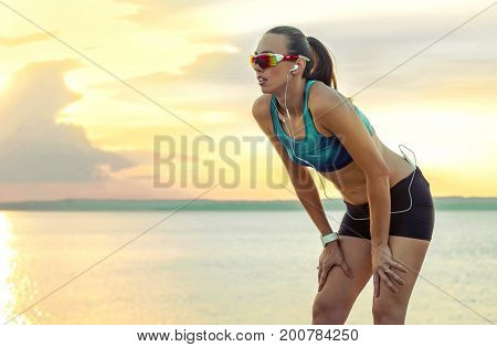 Running woman in sport sunglasses. Female runner with her smartphone training outdoor workout on beach. Beautiful fit mixed race Fitness model outdoors.