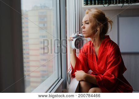 Beautiful young girl in the early morning by the window in silk red pajamas couldn't wake up