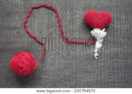 Crocheted red heart on a grunge board with a ball of woolen yarn. The heart is not finished.