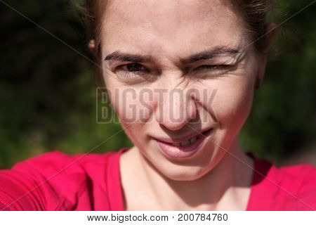 Selfie of happy beautiful Caucasian woman outdoors on a sunny summer day.