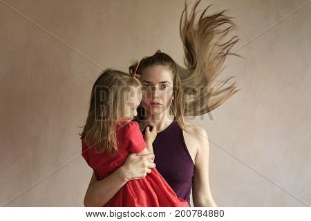 Young beautiful woman with long flying hair and her 4-year-old daughter in a red dress taking selfie together. The girl is holding a remote control for a photo camera. Shot with a soft focus and window light.